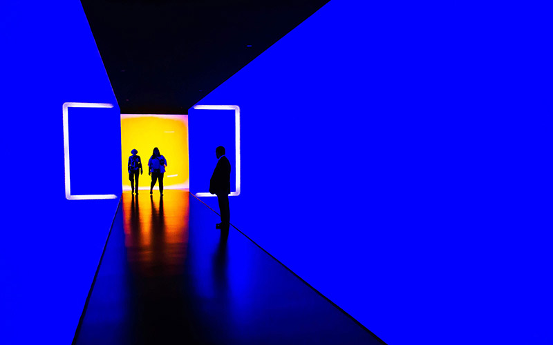Three people in a blue corridor with a yellow end.