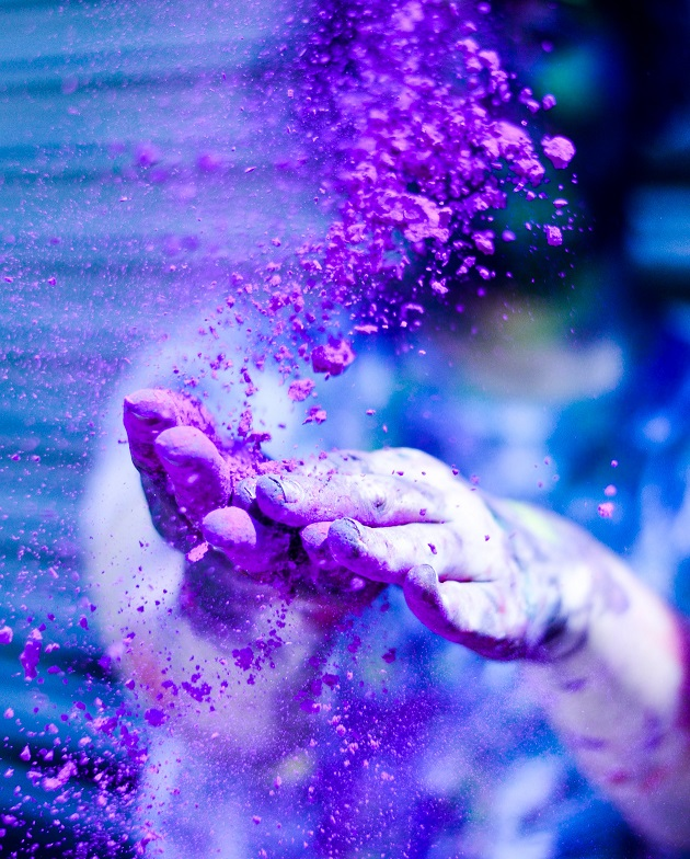 Two hands with purple dust all over.