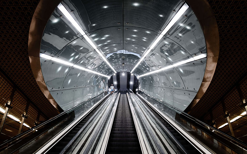 Escalator in a tunnel with silver ceiling.