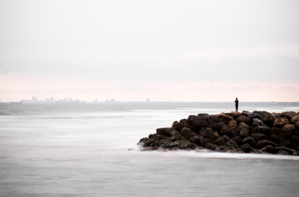 Lone person standing on a pier looking out over the sea towards a city skyline on the horizon