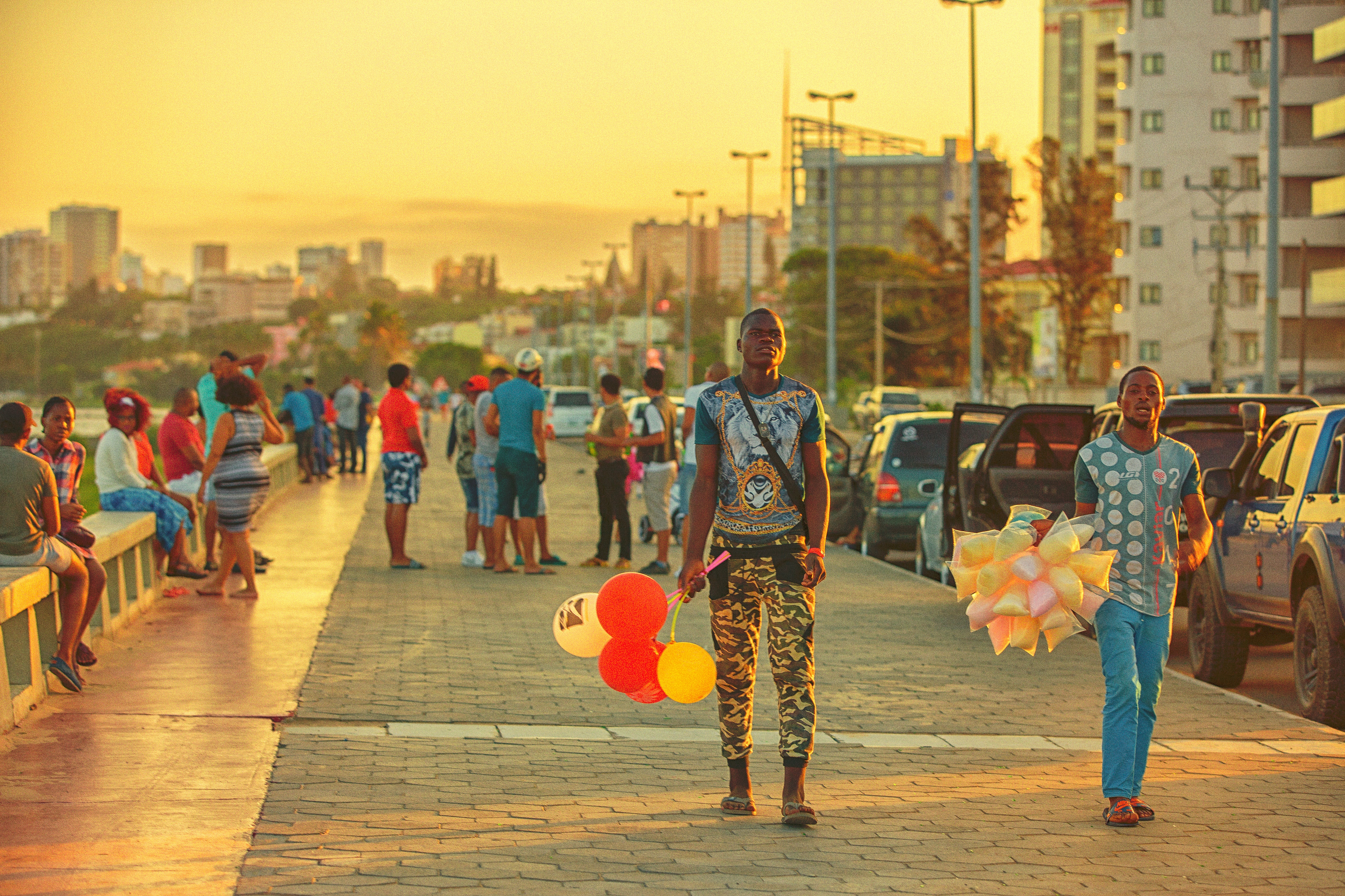 People along Avenida Marginal in the sunset in Maputo, Mozambique.