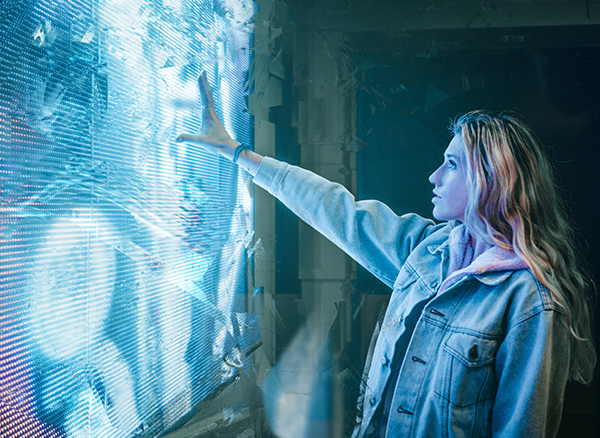 Woman standing infront of a wall touching a digital screen