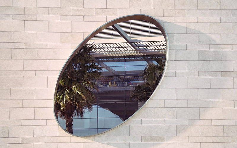 A light wall with an oval mirror reflecting palm trees